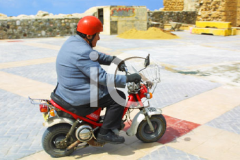 Royalty Free Photo of a Man Riding a Scooter