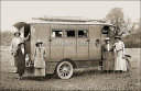 Royalty Free Photo of a Group of Women Standing Beside a Caravan