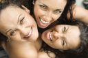 Royalty Free Photo of Three Women Embracing Each Other Looking Up and Smiling