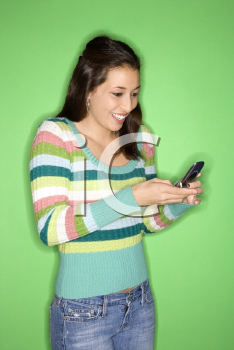 Royalty Free Photo of a Smiling Teen Girl Dialing on Her Cellphone Smiling