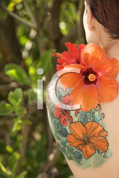 Royalty Free Photo of Back view of tattooed Caucasian woman with Hibiscus flower over her shoulder in Maui, Hawaii, USA