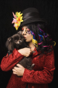 Royalty Free Photo of a Woman Wearing Unique Makeup Holding a Pomeranian