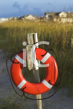 Royalty Free Photo of a Life Preserver Hanging on a Post on a Beach
