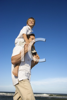 Royalty Free Photo of a Father With a Preteen on His Shoulders on a Beach