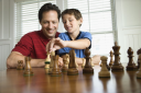 Royalty Free Photo of a Father Teaching Chess to His Son