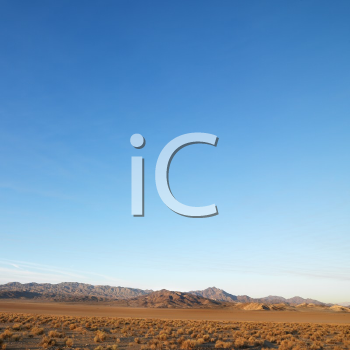 Royalty Free Photo of Barren Desert Landscape With Mountains in the Distance