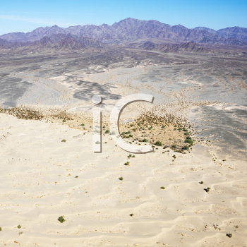 Aerial view of remote California desert with mountain range in background.