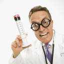 Royalty Free Photo of a Doctor Wearing Eyeglasses Holding an Over-sized Syringe