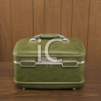 Royalty Free Photo of a Vintage Green Luggage Piece on a Wooden Desk