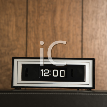 Royalty Free Photo of a Retro Alarm Clock Set for 12:00 Against Wood Paneling