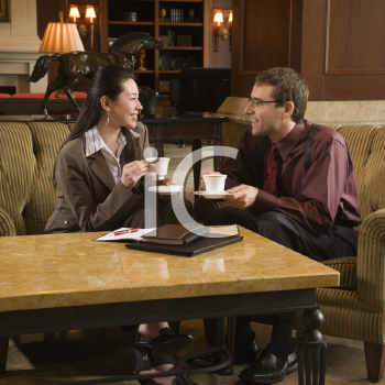 Royalty Free Photo of a Businessman and Businesswoman Drinking Coffee Conversing