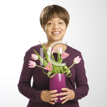 Royalty Free Photo of a Woman Holding a Vase of Pink Tulips Smiling