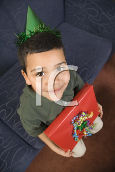 Royalty Free Photo of a Boy Wearing a Party Hat Holding a Present and Smiling