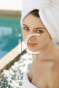 Royalty Free Photo of a Woman a Wearing Robe and Towel Sitting Next to a Pool