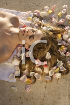 Royalty Free Photo of a Woman Lying Down With Rose Petals in Her Hair