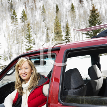 Royalty Free Photo of a Pretty Woman Sitting in a Car in Rural Snowy Colorado