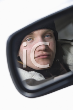 Royalty Free Photo of a Male Teenager Looking at Himself in a Side View mirror of a Car