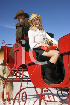Royalty Free Photo of a Woman Holding a Present in a Horse-Drawn Sleigh