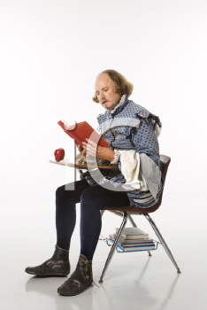 Royalty Free Photo of William Shakespeare in Period Clothing Sitting in a School Desk Reading a Book