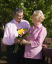 Royalty Free Photo of an Older Man Giving a Woman Flowers