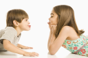 Royalty Free Photo of a Girl and Boy Sticking Their Tongues Out at Each Other