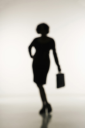 Royalty Free Photo of a Soft Focus Silhouette of a Businesswoman Holding a Briefcase