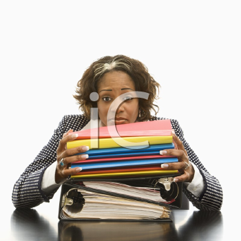 Royalty Free Photo of a Businesswoman Resting Her Head on a Large Stack of Books and Files