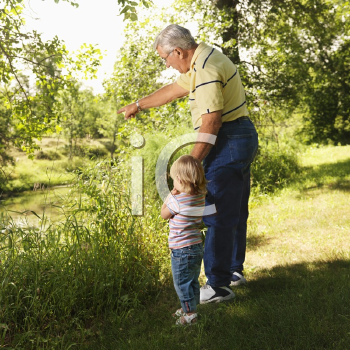 Royalty Free Photo of a Grandfather Holding Granddaughter's Hand by a Creek