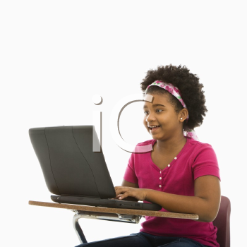 Royalty Free Photo of a Girl Sitting in a School Desk Typing on a Laptop