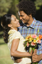 Royalty Free Photo of a Man Giving a Smiling Woman a Bouquet of Flowers