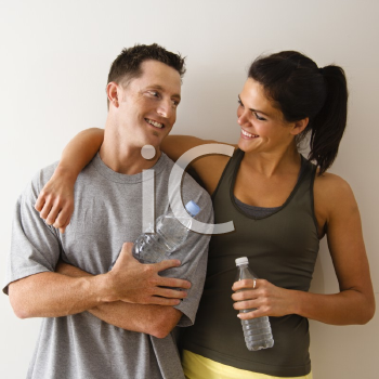 Royalty Free Photo of Man and Woman at a Gym in Fitness Attire Holding Water Bottles Smiling at Each Other