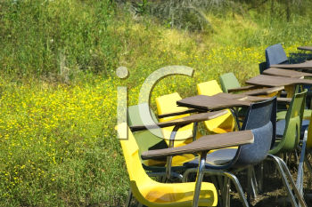 Royalty Free Photo of a Bunch of Old School Chairs in a Grassy Field