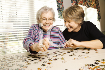 Elderly woman and a younger woman work on a jigsaw puzzle.  Horizontal shot.