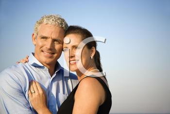 Attractive married couple hug and smile with a blue sky in the background. Horizontal shot.