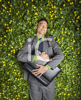 Young businessman with briefcase relaxing in a flower patch smiling with contentment.