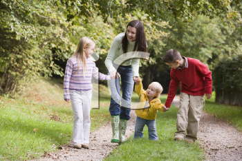 Royalty Free Photo of a Woman and Three Children Walking on a Trail