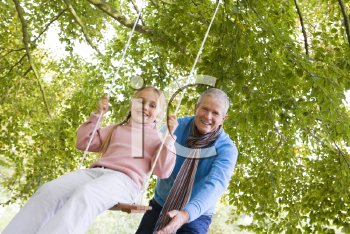 Royalty Free Photo of a Man Pushing a Girl on a Swing