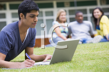 Royalty Free Photo of a Student Working on a Laptop With Other People in the Background