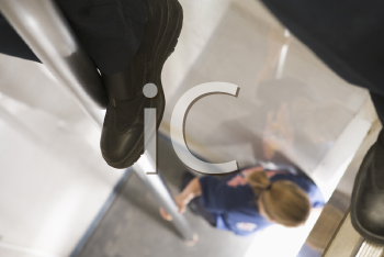 Royalty Free Photo of a Firefighter's Legs on the Pole With a Female at the Bottom