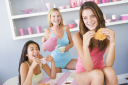 Royalty Free Photo of Three Young Women Having Tea and Pastries