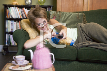 Royalty Free Photo of a Woman Lying on a Couch Holding a Remote and Eating Potato Chips