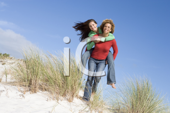 Royalty Free Photo of a Girl Giving a Girl a Piggyback Ride on Sand