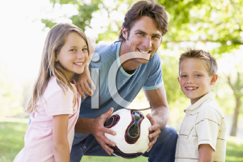 Royalty Free Photo of a Man and Two Children With a Ball