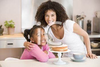 Royalty Free Photo of a Mother and Daughter With Cake and a Coffee