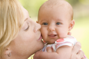 Royalty Free Photo of a Mother Kissing a Baby