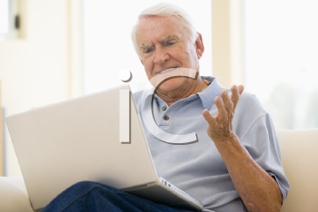 Royalty Free Photo of a Man With a Laptop Looking Frustrated