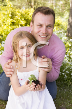 Royalty Free Photo of a Father and Daughter Holding a Plant
