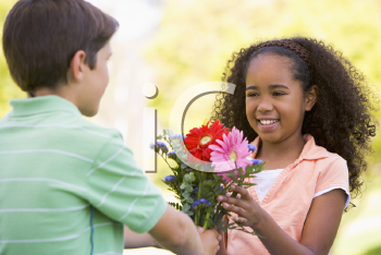Royalty Free Photo of a Boy Giving a Girl Flowers