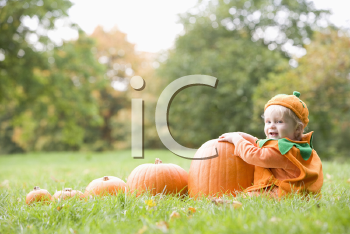 Royalty Free Photo of a Baby in a Pumpkin Costume With Pumpkins