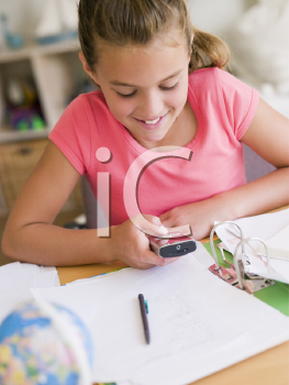 Royalty Free Photo of a Young Girl Doing Homework and Using a Cellphone
